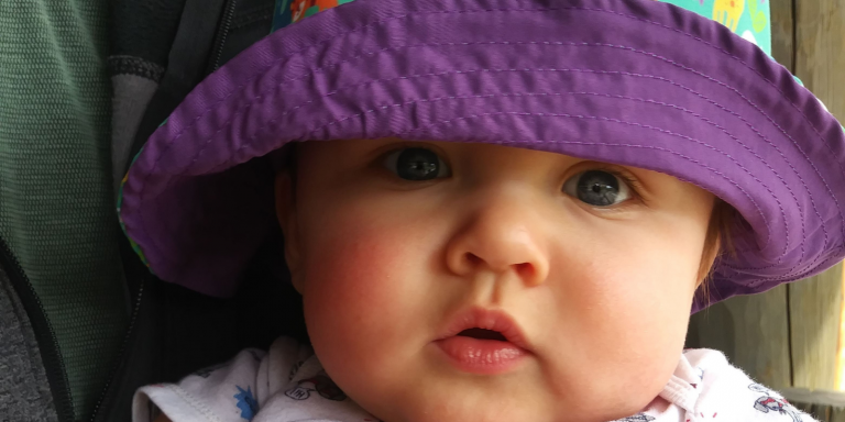 Baby staring at camera with sunhat on