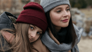 2 women sitting close and side by side, wearing warm clothes